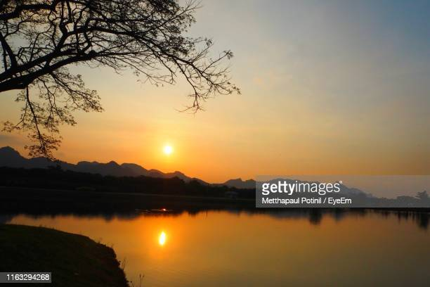 scenic view of lake against romantic sky at sunset - metthapaul stock photos and pictures