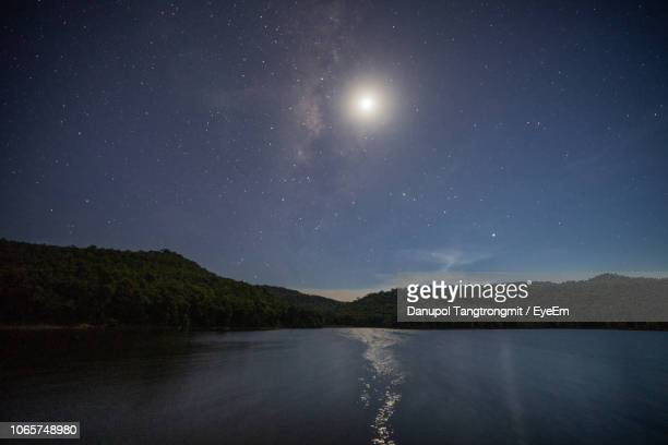 scenic view of lake against sky at night - moonlight stock pictures, royalty-free photos & images