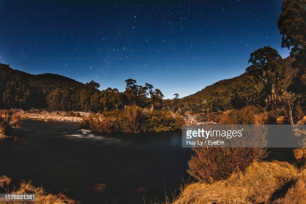 scenic view of lake against sky at night - snowcapped mountain stock pictures, royalty-free photos & images