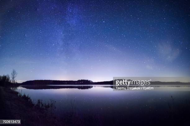scenic view of lake against sky at night - teemu tretjakov stock pictures, royalty-free photos & images