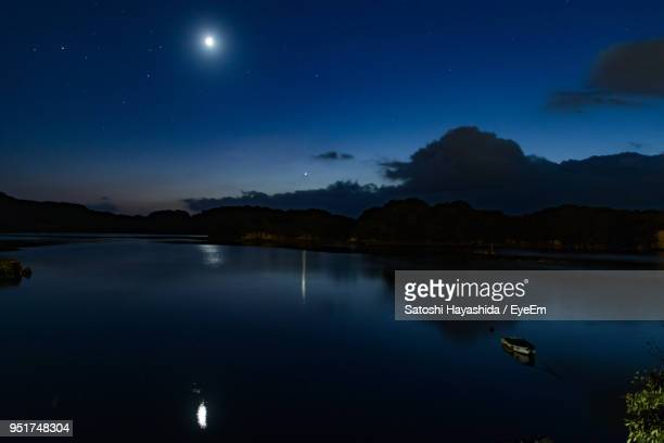 scenic view of lake against sky at night - 月の光 ストックフォトと画像