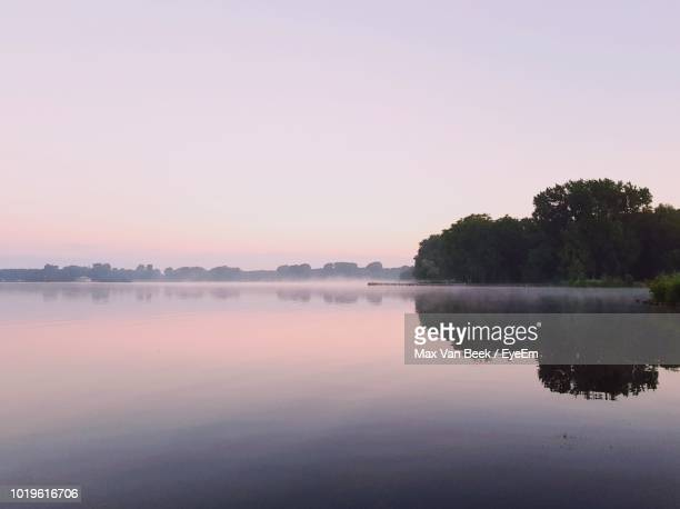 scenic view of lake against sky at sunset - reflection lake stock photos and pictures