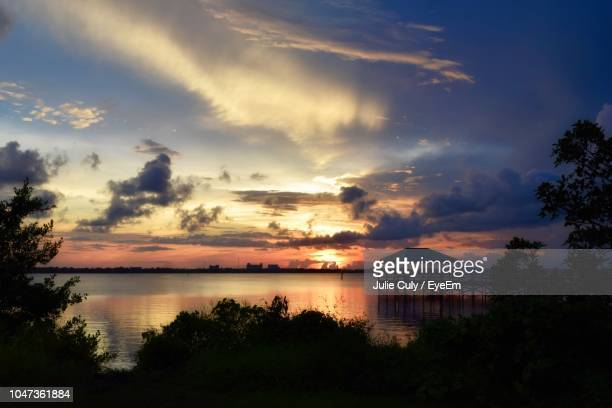 scenic view of lake against sky at sunset - julie culy stock pictures, royalty-free photos & images