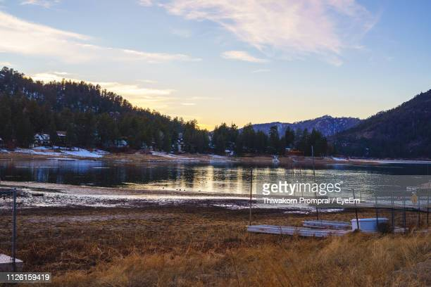 scenic view of lake against sky at sunset - big bear lake stock photos and pictures