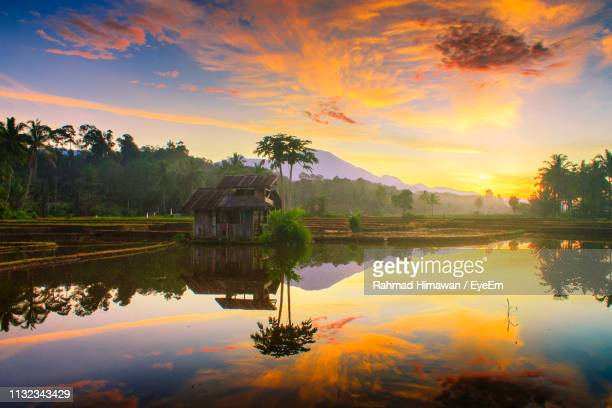 scenic view of lake against sky at sunset - rahmad himawan stock photos and pictures