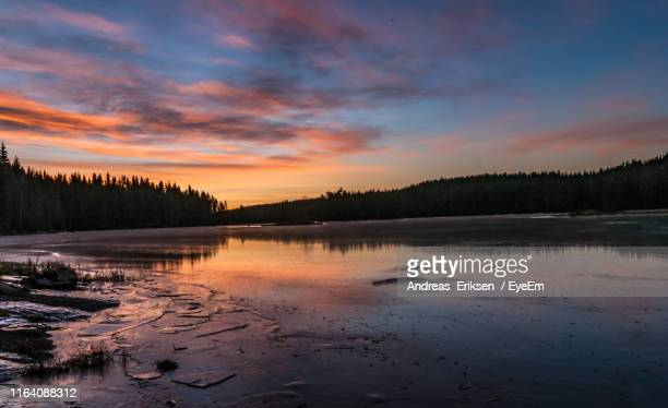 scenic view of lake against sky at sunset - eriksen stock pictures, royalty-free photos & images