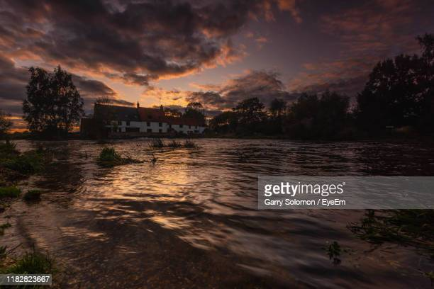 scenic view of lake against sky at sunset - great doddington stock photos and pictures