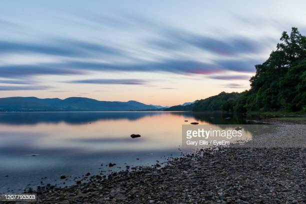 scenic view of lake against sky at sunset - loch stock pictures, royalty-free photos & images