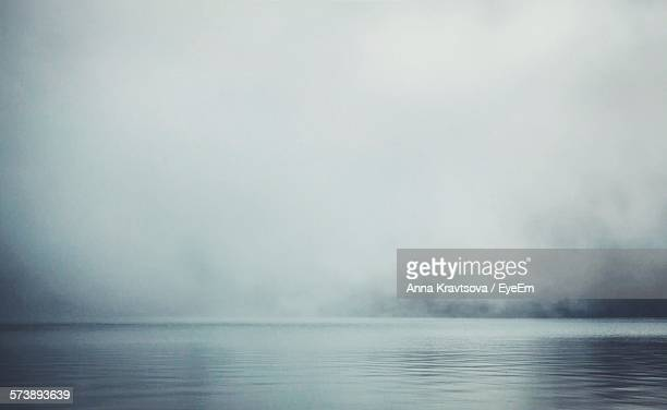 scenic view of lake against sky during foggy weather - mist stockfoto's en -beelden