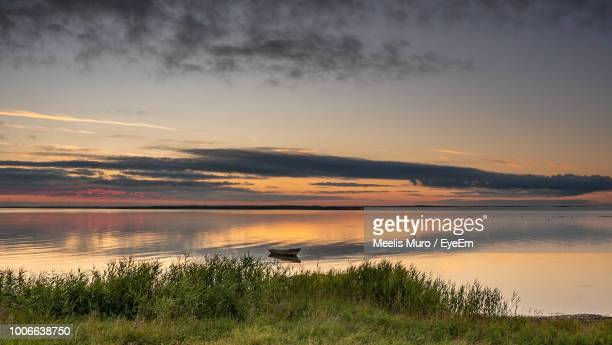 scenic view of lake against sky during sunset - muro stock photos and pictures
