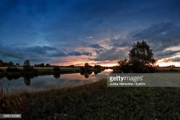 scenic view of lake against sky during sunset - heinovirta stock photos and pictures