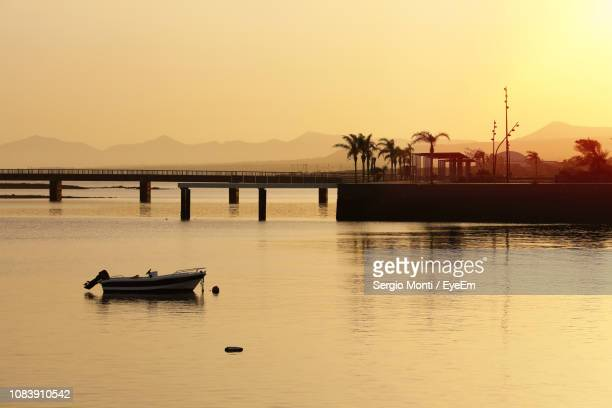 scenic view of lake against sky during sunset - arrecife stock photos and pictures