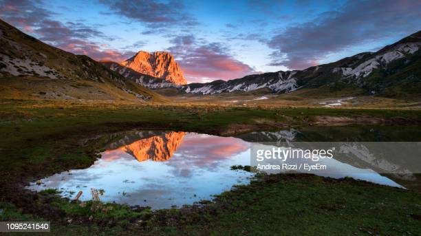scenic view of lake against sky during sunset - andrea rizzi stockfoto's en -beelden