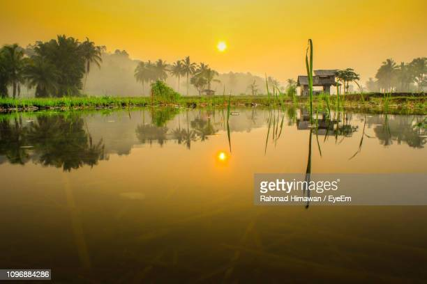 scenic view of lake against sky during sunset - rahmad himawan stock photos and pictures