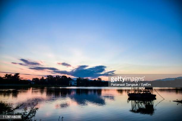 scenic view of lake against sky during sunset - pattanasit stock pictures, royalty-free photos & images