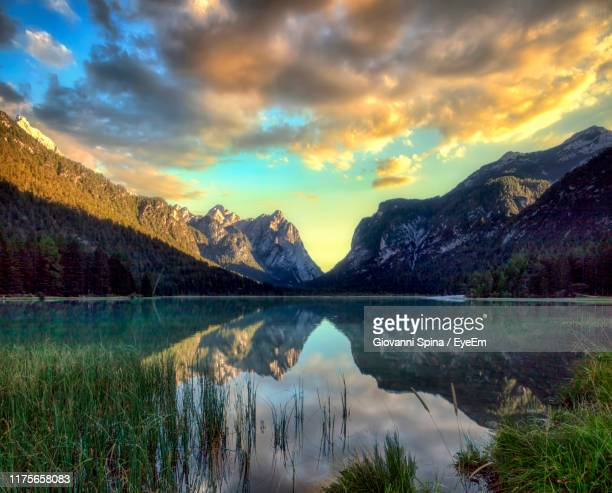 scenic view of lake against sky during sunset - toblach stock photos and pictures