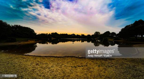 scenic view of lake against sky during sunset - andy rinkoff stock pictures, royalty-free photos & images
