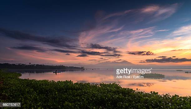 scenic view of lake against sky during sunset - ade rizal stock photos and pictures
