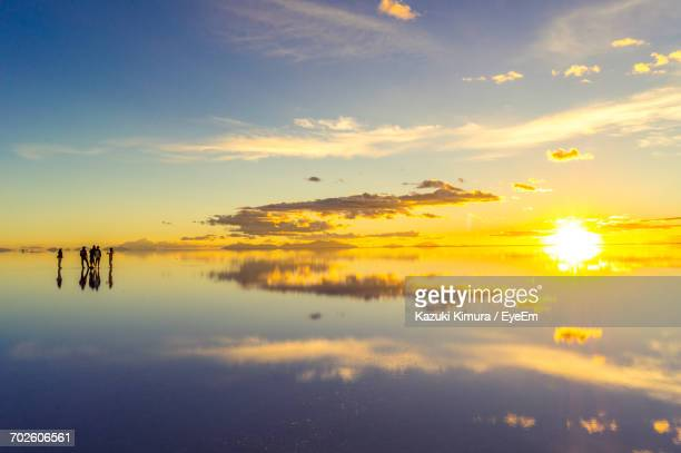 scenic view of lake against sky during sunset - ウユニ塩湖 ストックフォトと画像
