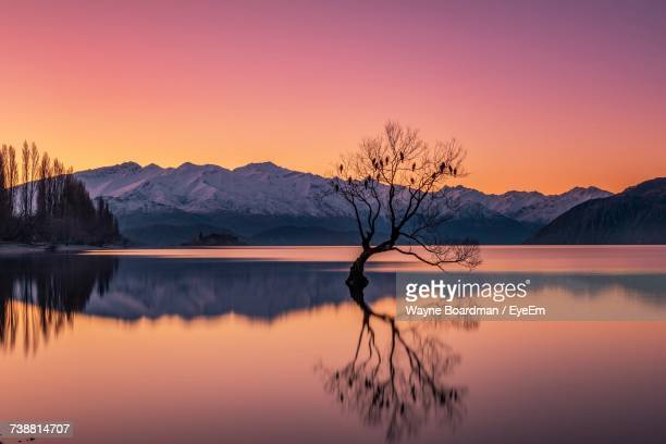 scenic view of lake against sky during sunset - reflection lake stock photos and pictures
