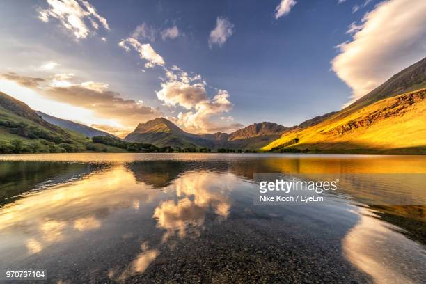 scenic view of lake against sky during sunset - english lake district stock photos and pictures