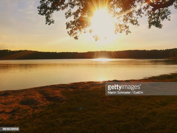 scenic view of lake against sky during sunset - küste stock-fotos und bilder