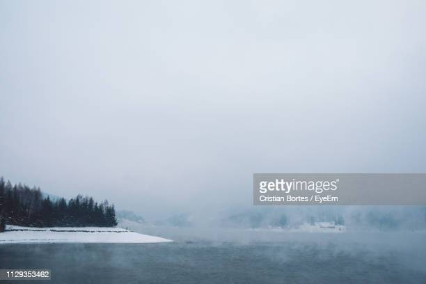 scenic view of lake against sky during winter - bortes stock pictures, royalty-free photos & images
