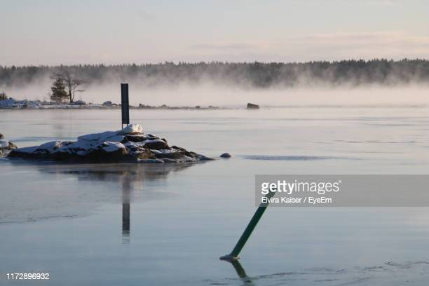 scenic view of lake against sky during winter - vista lateral stock pictures, royalty-free photos & images