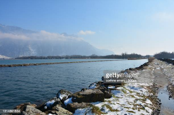scenic view of lake against sky during winter,switzerland - corinne paradis photos et images de collection