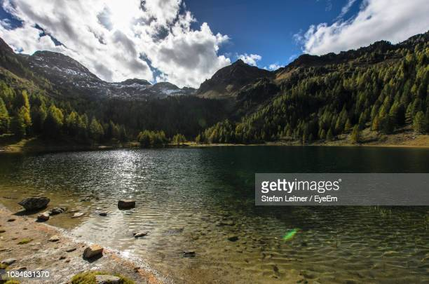 scenic view of lake against sky - schladming stock pictures, royalty-free photos & images
