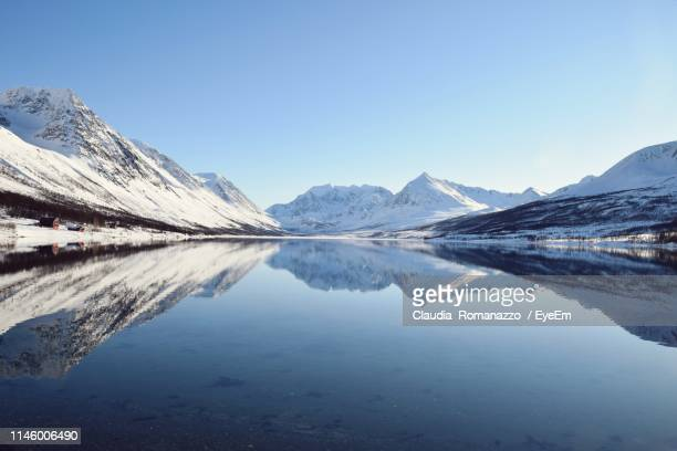 scenic view of lake against snowcapped mountains - claudia romanazzo foto e immagini stock