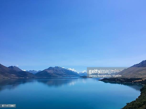Scenic View Of Lake Amidst Mountains Against Clear Blue Sky
