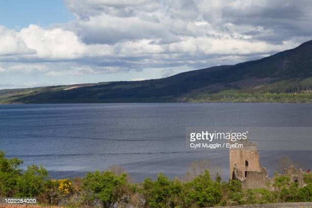 scenic view of lake and buildings against sky - drumnadrochit stock pictures, royalty-free photos & images