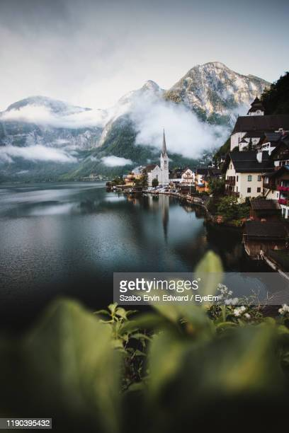 scenic view of lake and buildings against sky - upper austria stock pictures, royalty-free photos & images