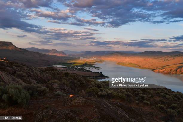 scenic view of lake and landscape against sky during sunset - kamloops stock pictures, royalty-free photos & images