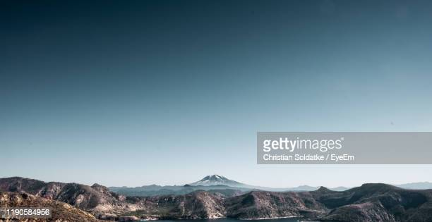 scenic view of lake and mountain range against clear sky - christian soldatke stock pictures, royalty-free photos & images