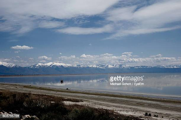 Scenic View Of Lake And Mountain Range Against Cloudy Sky