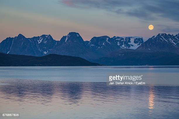 Scenic View Of Lake And Mountain Range Against Sky At Dusk