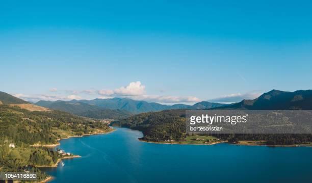 scenic view of lake and mountains against blue sky - bortes bildbanksfoton och bilder