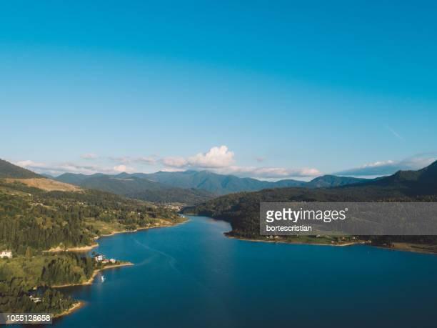 scenic view of lake and mountains against blue sky - bortes fotografías e imágenes de stock
