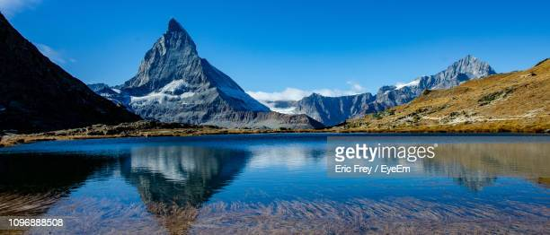 scenic view of lake and mountains against blue sky - matterhorn stock pictures, royalty-free photos & images