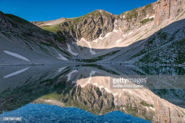scenic view of lake and mountains against blue sky - andrea rizzi stockfoto's en -beelden