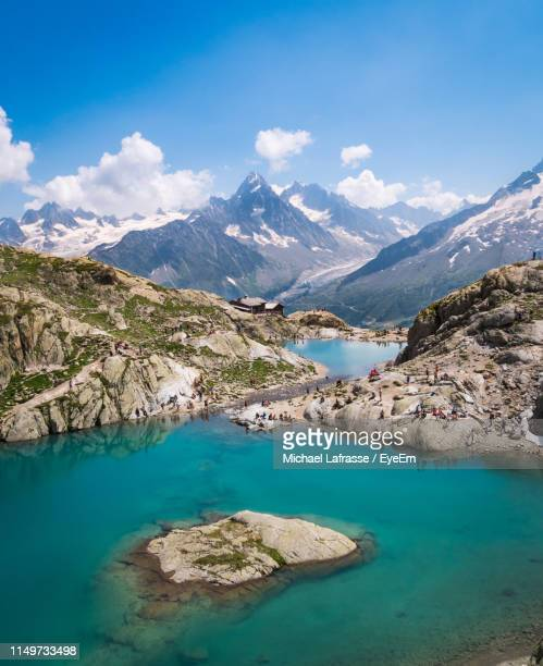 scenic view of lake and mountains against blue sky - chamonix stock pictures, royalty-free photos & images