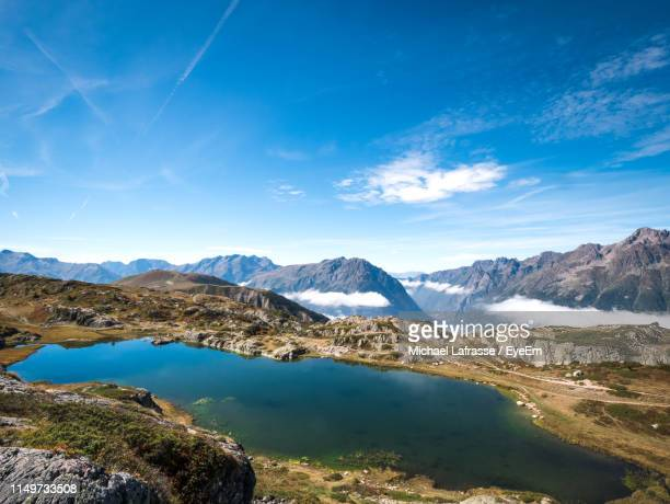 scenic view of lake and mountains against blue sky - イゼール県 ストックフォトと画像