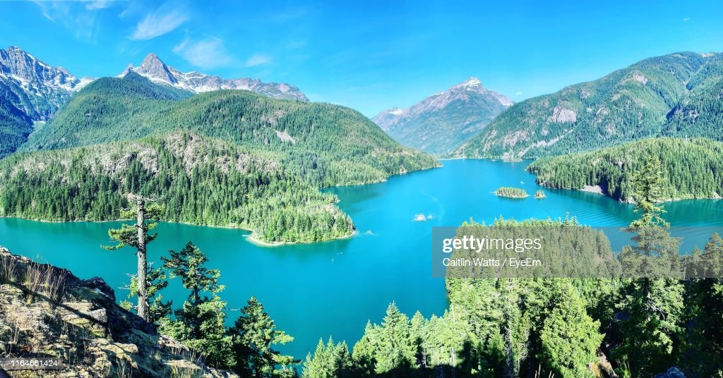 Scenic View Of Lake And Mountains Against Blue Sky : Stock Photo