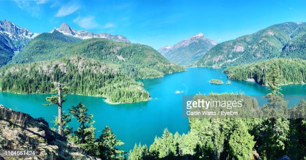scenic view of lake and mountains against blue sky - diablo lake stock photos and pictures