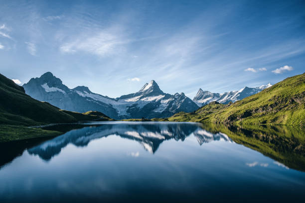 scenic view of lake and mountains against blue sky - horizontal stock pictures, royalty-free photos & images