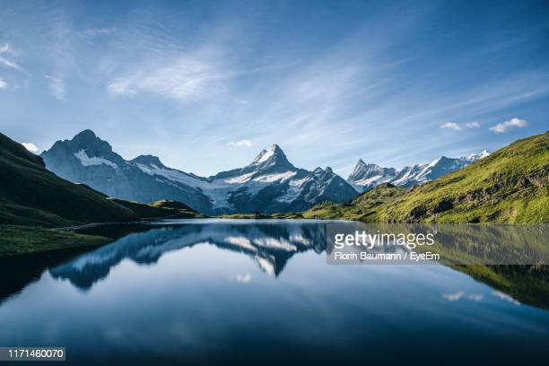 scenic view of lake and mountains against blue sky - horizontal stock-fotos und bilder
