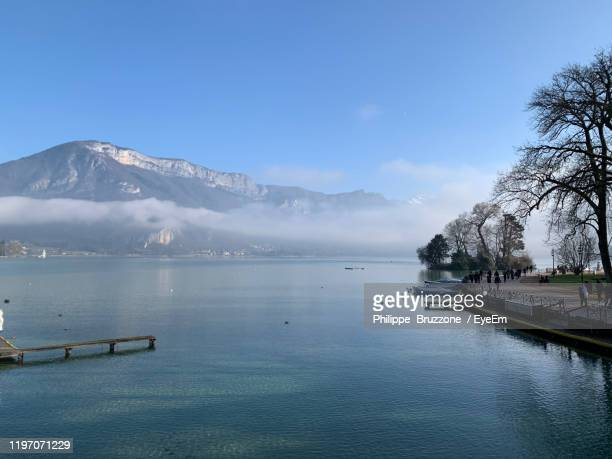 scenic view of lake and mountains against blue sky - annecy photos et images de collection