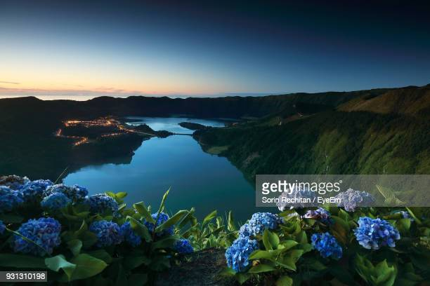 scenic view of lake and mountains against blue sky - ponta delgada stock photos and pictures